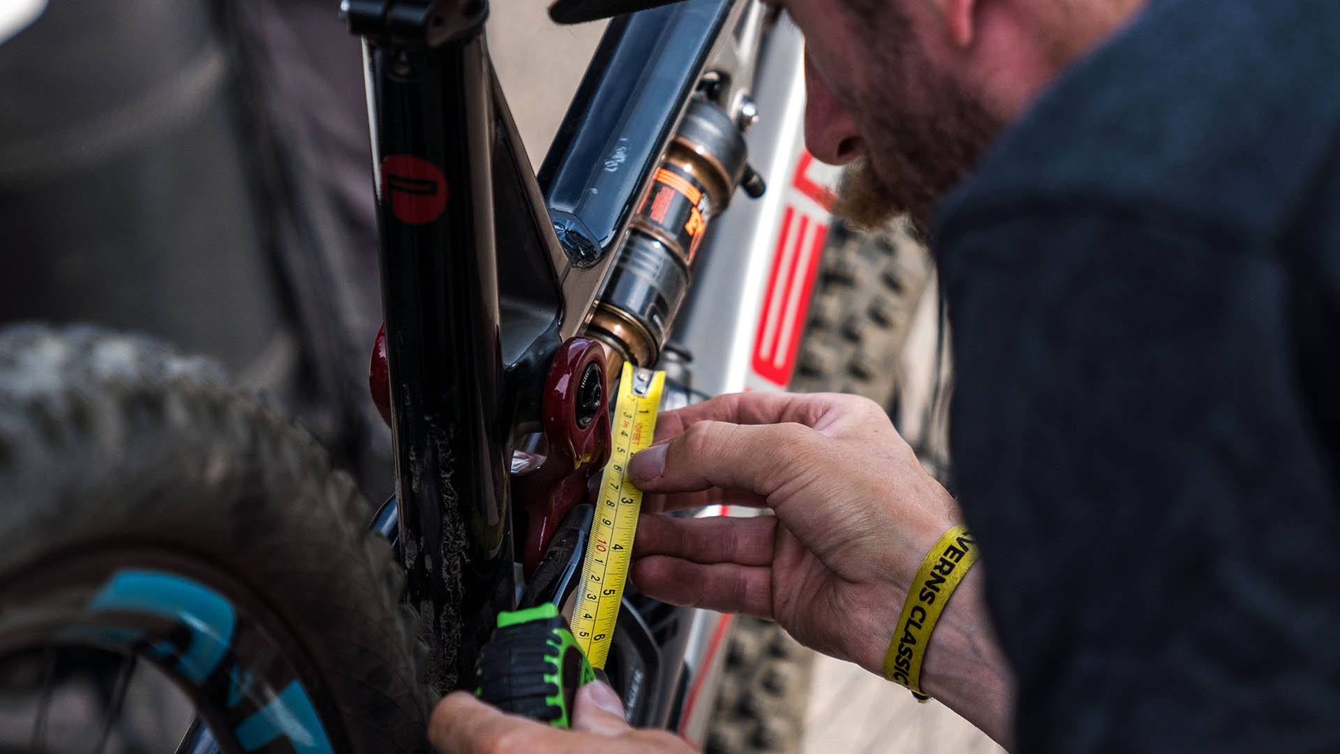 +3 Suspension Expert Will Soffe checking the sag level on a Fox Racing Shox air shock on a rider's Intense Sniper