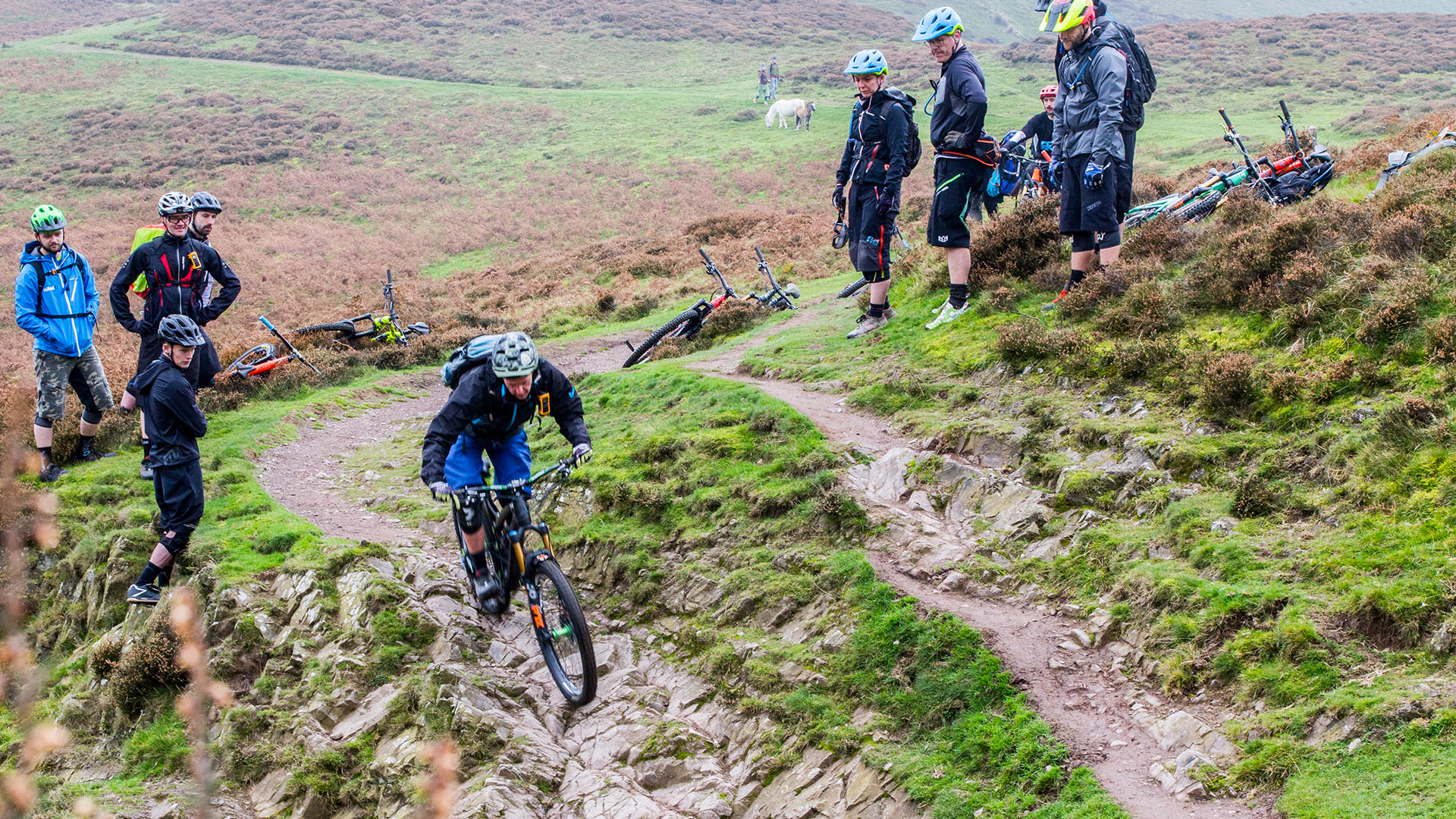 +3 MTB Coach Sandy Plenty shows riders a line down a tricky natural corner high on the Long Mynd in Shropshire
